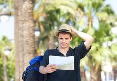 Lost tourist with bag holding map Stock Photos