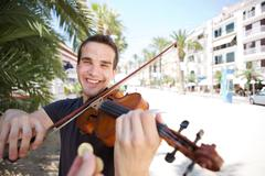Street performer playing violin being paid money Stock Photos