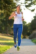 Active woman running in park Stock Photos