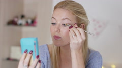 4K Attractive young woman putting on make-up in bedroom. - stock footage