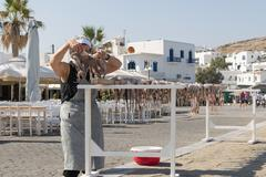 Old lady at Paros island hanging an octopus outside a tavern to dry in the sun. - stock photo