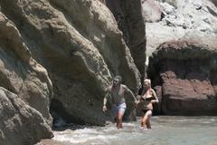 Couple at Kalogeros beach taking a healing mud bath with clay. Stock Photos