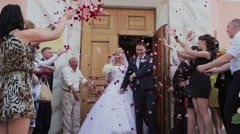 Newly wed couple being showered in rose petals Stock Footage