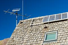 Photovoltaic panels on the roof of a hut - stock photo