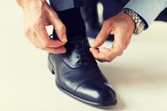Close up of man leg and hands tying shoe laces Stock Photos