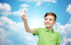 Happy boy in green polo t-shirt pointing finger up Stock Photos