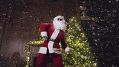 Santa Claus in sunglasses dancing and looking at the camera, tracking shot Stock Footage