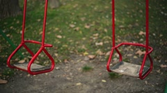 Empty swing seat swaying in park playground Stock Footage