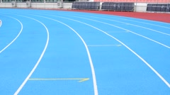 Stock Video Footage of Young Asian boy running on blue track in the stadium