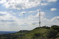 Paragliding around a television tower on the Hesselberg - stock photo