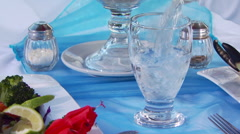 Waiter pouring water in glass on set table Stock Footage
