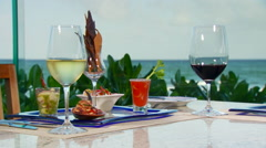 Wine and appetizer set on table near seashore - stock footage