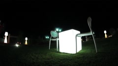 Lit table with two chairs in the garden Stock Footage