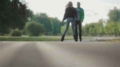 Young attractive couple rollerblading and doing tricks with skates in park - stock footage