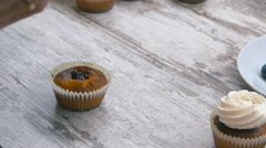 Stock Video Footage of Cooking cupcakes. Apply cream. Close-up.