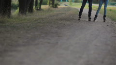 Male and female rollerblade synchronously on the forest path on a summer day Stock Footage