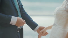 Groom putting a ring on brides finger at beautiful sea background. Close up Stock Footage