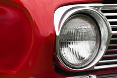 Stock Photo of Close-up of left headlight of a red shiny classic vintage car