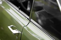 Car handle of a green shiny classic vintage car - stock photo