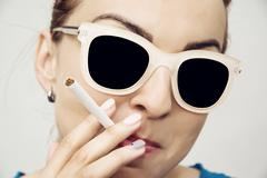 Young caucasian woman smoking cigarette, bad habit - stock photo
