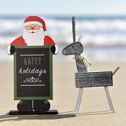 reindeer and santa claus with text happy holidays on the beach - stock photo