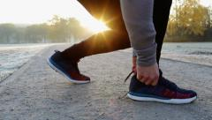Young man tie shoes and run at cold winter morning - stock footage