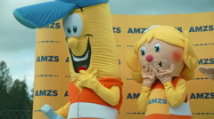 Three ornage and white mascots are communicating with one another Stock Footage