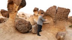 Asian man pose at mushroom rock, make fun superman move, Yehliu Geopark Stock Footage