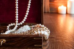Wooden box of jewels and jewelry on a background of burning candles - stock photo