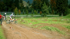 Two motorbikers are overcoming bumps on a road track together Stock Footage