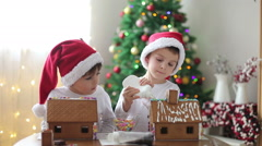 Two sweet boys, brothers, making gingerbread cookies house Stock Footage