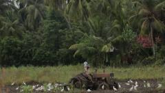 A man works on a tractor in a large field of tropical. Sri Lanka Stock Footage