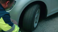 A mechanic is demonstrating how to make a flat tyre on a car Stock Footage