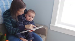 A dolly shot of mother reading book to baby boy Stock Footage