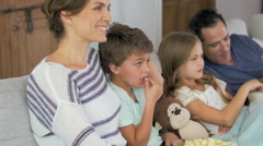 Family eating pocorn watching movie together Stock Footage