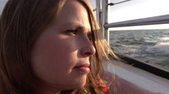 Girl looking into sunset off side of boat on ocean 4k Stock Footage