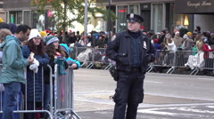 Police officer standing along fence of 89th annual Macy's Parade route 4k Stock Footage