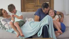 Family tickle fight on couch at home with kids jumping to surprise parents Stock Footage