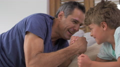 Father and son arm wrestling on couch in living room Stock Footage