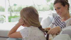 Mom tying daughters hair Stock Footage