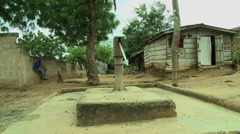GHANA MAN SITTING BEHIND A BOREHOLE WATER PUMP Stock Footage