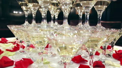 The waiter pours champagne in glass tower of champagne coctail restaurant Stock Footage