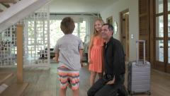 Children running to greet dad father after arriving home from work business trip - stock footage