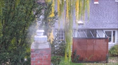 Steam rising from a chimney over a house Stock Footage