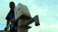 GHANA UP ANGLE OF MAN PUMPING BOREHOLE WATER Stock Footage