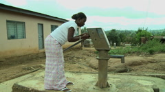 GHANA WOMAN UNLOCKING BOREHOLE WATER PUMP Stock Footage
