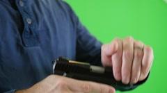 Slow motion green screen shot man loading bullet in pistol chamber - stock footage