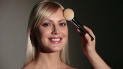 Makeup artist with powder brush, blushing face of model Stock Footage