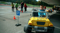 Little boy is driving a small car Stock Footage