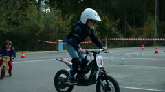 Young girl driving a motorbike and overcoming small bumps on a track Stock Footage